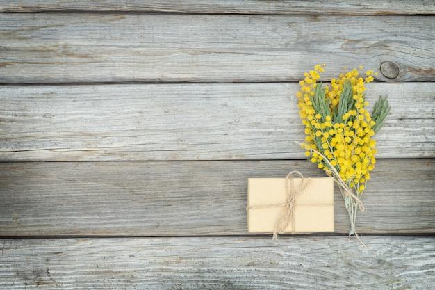 Caixa de presente ecológica com flores de mimosa em superfície de madeira cinza