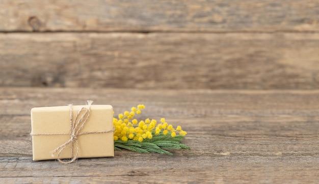 Caixa de presente ecologicamente correta com um raminho de mimosa na superfície de madeira