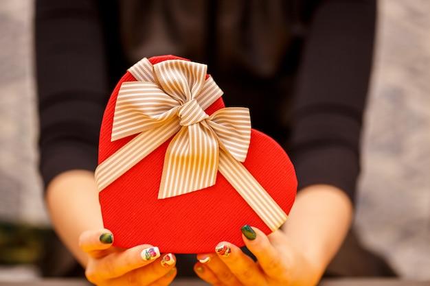 Caixa de presente em forma de coração biodegradável nas mãos das mulheres