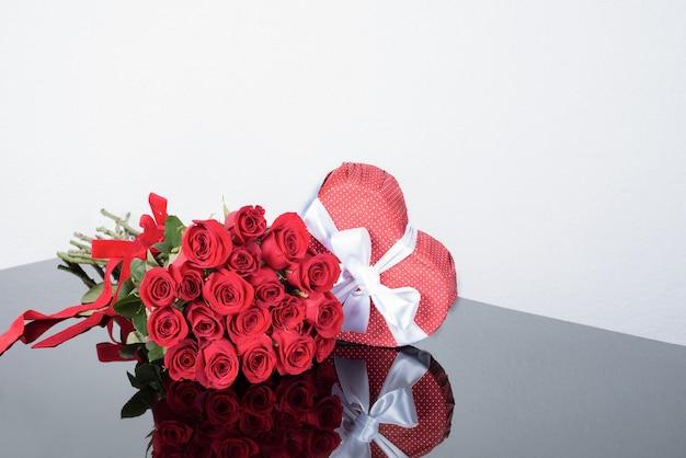 Caixa de presente em forma de coração, buquê de rosas em uma superfície de espelho.