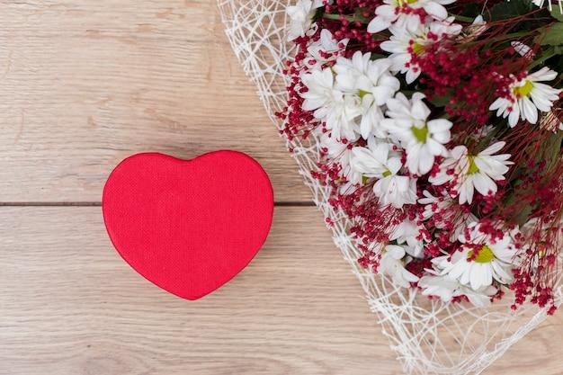 Caixa de presente em forma de coração com buquê de flores