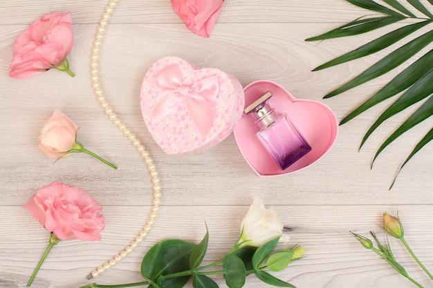 Caixa de presente em forma de coração com frasco de perfume e flores cor de rosa e folhas verdes sobre fundo de madeira. vista do topo. conceito de celebração.