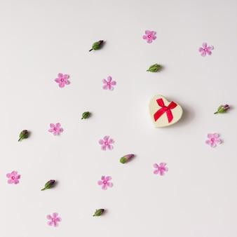 Caixa de presente em forma de coração com padrão de flores. postura plana.
