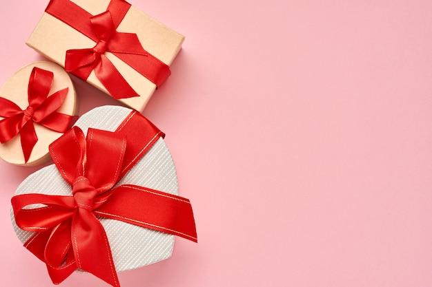 Caixa de presente em forma de coração com uma fita vermelha em fundo rosa. cartão postal do conceito de dia dos namorados. vista do topo.