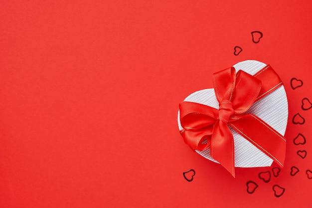 Caixa de presente em forma de coração com uma fita vermelha em um fundo vermelho. cartão postal do conceito de dia dos namorados. vista do topo.