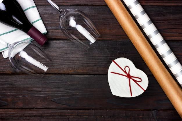 Caixa de presente em forma de coração, garrafa de vinho tinto e duas taças em uma mesa escura. vista de cima.