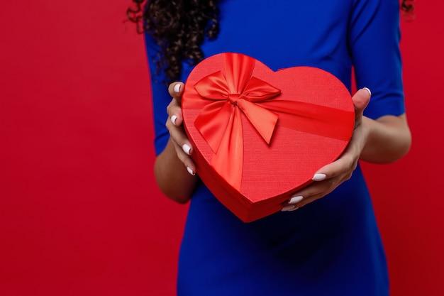 Caixa de presente em forma de coração nas mãos da mulher negra na parede vermelha