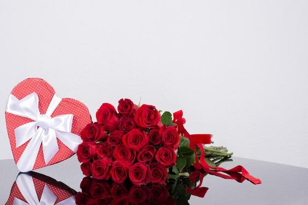 Caixa de presente em forma de coração, rosas clássicas do buquê em uma superfície de espelho.