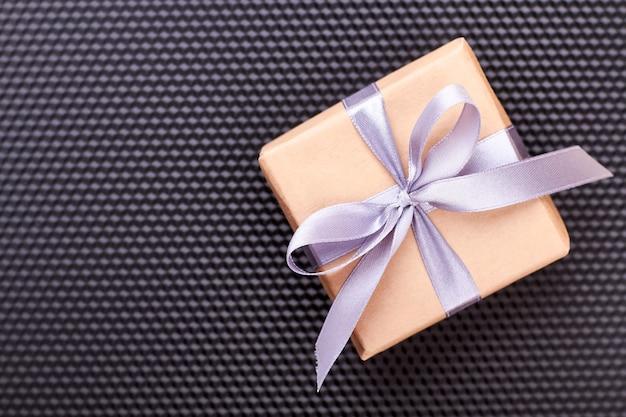 Caixa de presente em fundo preto. caixa de presente e laço de glicínias. arte de embrulhar presentes.