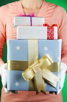 Caixa de presente em mão feminina na cor de fundo