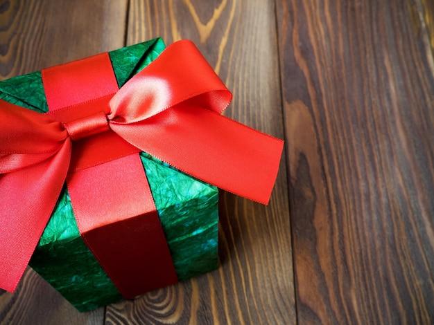 Caixa de presente em papel brilhante com laço na placa de madeira. conceito de férias