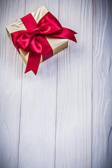 Caixa de presente em papel brilhante com laço no conceito de férias de tábua de madeira