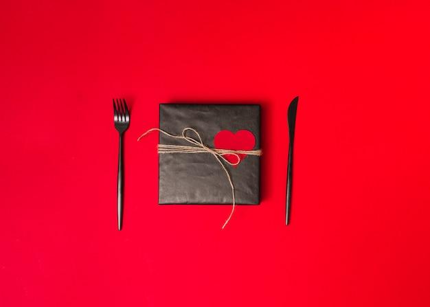 Caixa de presente em papel docinho com fio entre talheres