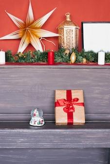 Caixa de presente em papel kraft com laço vermelho e decoração de natal no piano