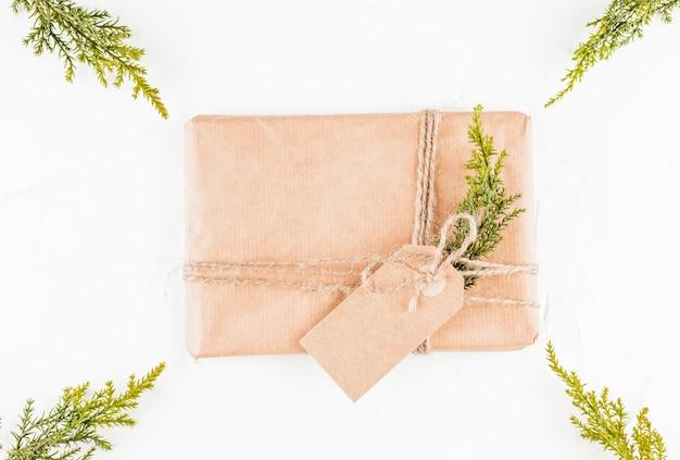 Caixa de presente em papel ofício com tag entre galhos de coníferas