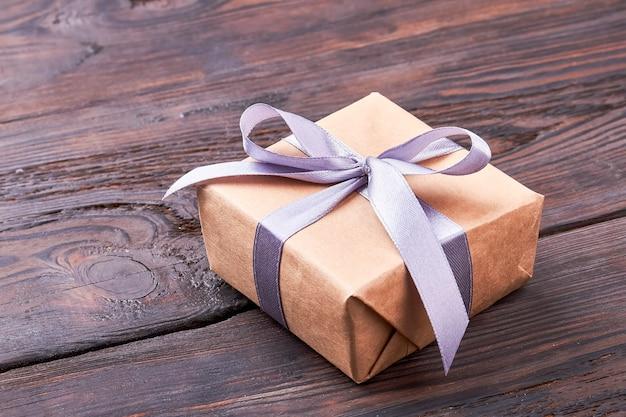 Caixa de presente em superfície de madeira. laço de fita na caixa de presente. modelo de um presente.