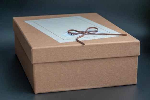 Caixa de presente em um fundo escuro contrastado, decorado com um laço texturizado