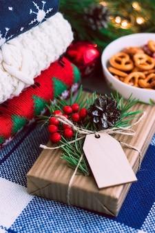 Caixa de presente em um invólucro de artesanato com um galho de visco de pinheiro e decorações de natal e ano novo