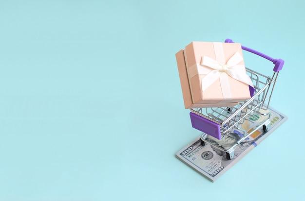 Caixa de presente em um pequeno carrinho de compras encontra-se em notas de um dólar em azul claro
