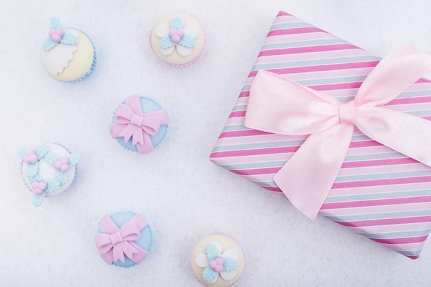 Caixa de presente embrulhada brilhante e bolos decorados