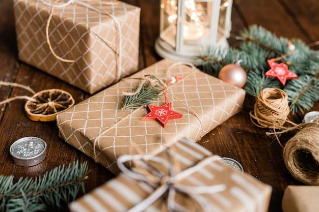 Caixa de presente embrulhada com decoração de conífera e estrela vermelha no topo, cercada por fios, velas e outras caixas