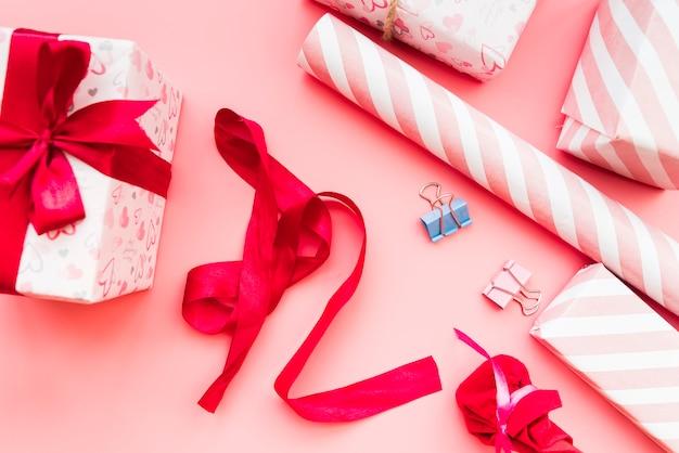 Caixa de presente embrulhada com fita vermelha; papel de presente e clipe de papel no fundo rosa