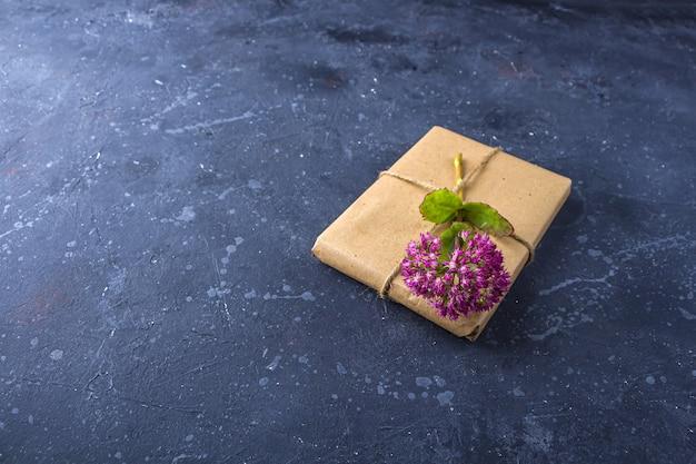 Caixa de presente embrulhada com papel artesanal e decorada com flor rosa