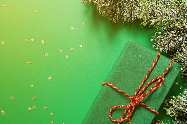 Caixa de presente embrulhada de natal e galhos de árvores em verde