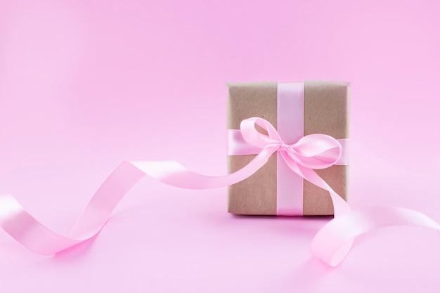 Caixa de presente embrulhada em papel artesanal com fita rosa