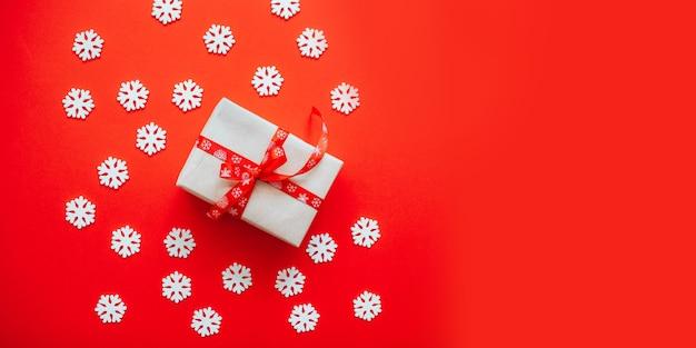 Caixa de presente embrulhada em papel artesanal com laço de fita vermelha