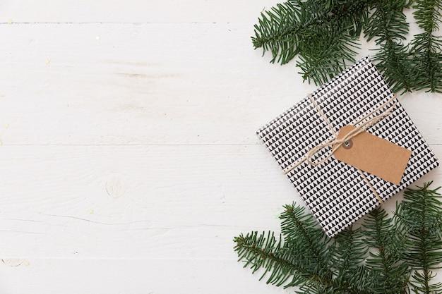 Caixa de presente embrulhada em papel e com fita adesiva e uma etiqueta em uma mesa de madeira branca com galhos de pinheiro