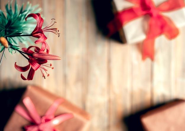 Caixa de presente embrulhada em papel kraft e uma flor de lírio vermelha em uma mesa de madeira.
