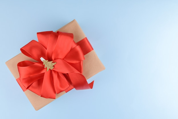 Caixa de presente embrulhada em papel kraft reciclado com laço de fita vermelha e árvore de natal dourada em um prendedor de roupa em um fundo azul pastel