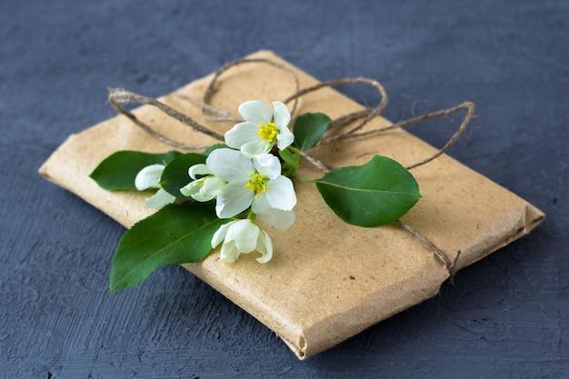 Caixa de presente embrulhada em papel pardo decorado com flor de macieira em um fundo escuro.