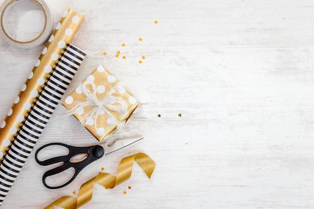 Caixa de presente embrulhada em papel pontilhado dourado e materiais de embalagem