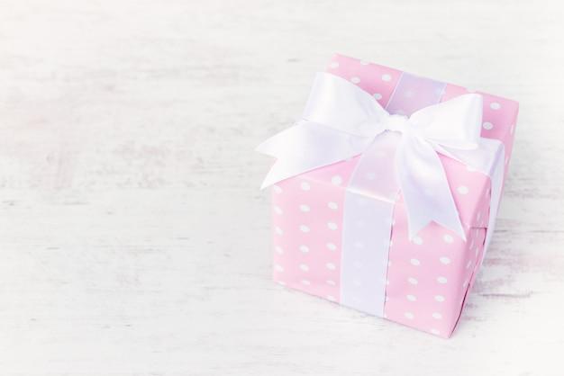 Caixa de presente embrulhada em papel pontilhado rosa e laço de cetim amarrado sobre madeira branca.
