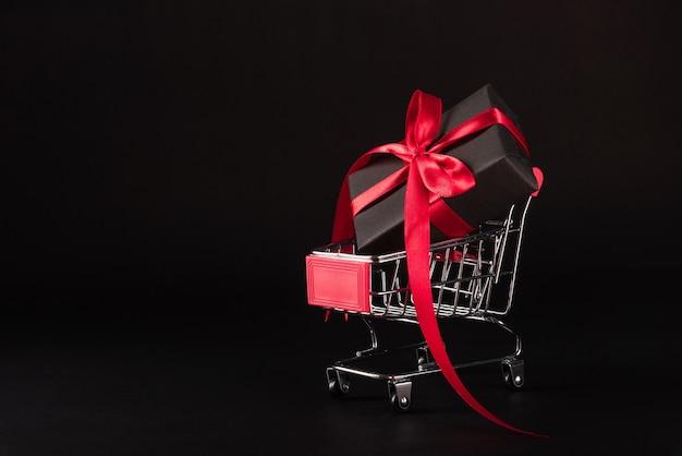 Caixa de presente embrulhada em papel preto e fita vermelha presente no carrinho de compras