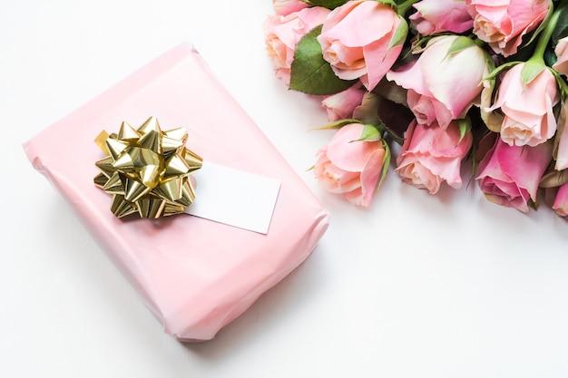 Caixa de presente embrulhada em papel rosa com uma fita ao lado de um buquê de lindas rosas