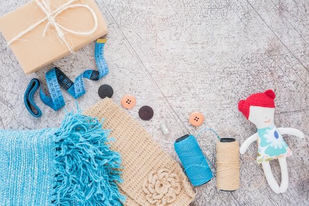 Caixa de presente embrulhado; fita métrica; botões; carretel e boneca no pano de fundo texturizado