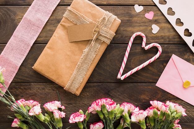 Caixa de presente entre flores, envelope e bastões de doces