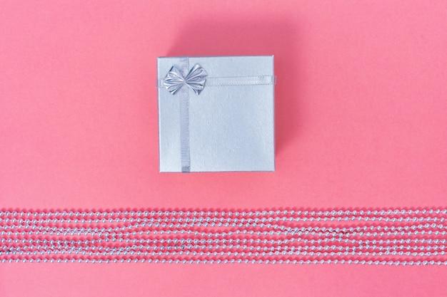 Caixa de presente fechada prata brilhante na cor rosa de papel. composição de estilo minimalista.