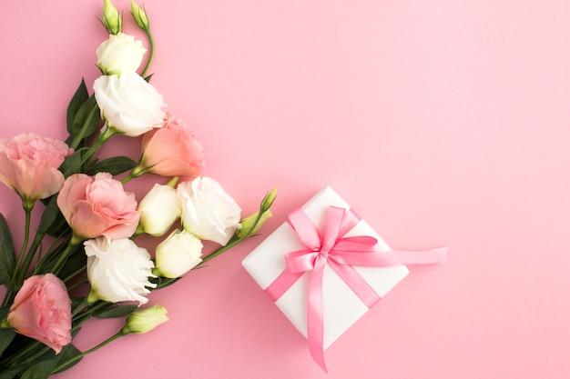 Caixa de presente, flores brancas e rosa no fundo rosa com espaço de cópia