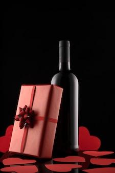 Caixa de presente, garrafa de vinho e corações vermelhos na superfície preta.