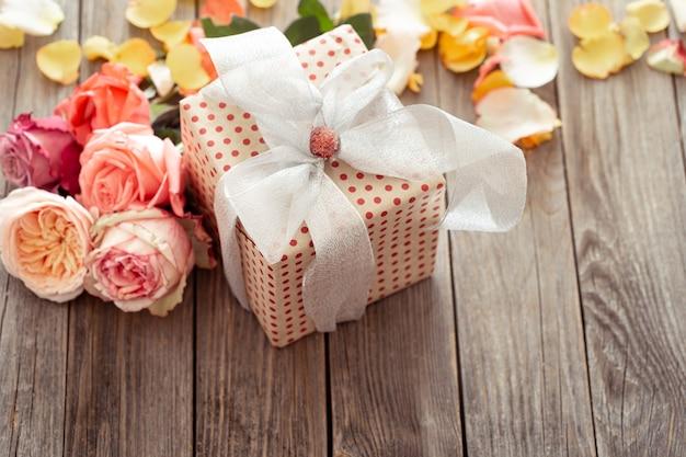 Caixa de presente lindamente embrulhada e rosas frescas