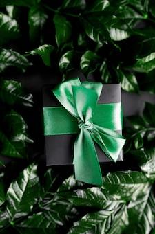 Caixa de presente luxuosa preta com fita verde em fundo escuro com folhas nas laterais