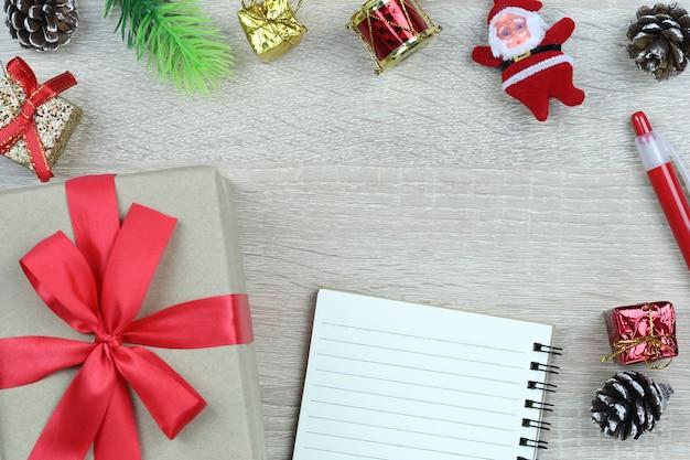 Caixa de presente marrom com laço vermelho no chão de madeira e livro em branco no natal e ano novo conce