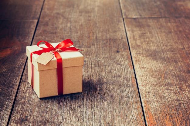 Caixa de presente marrom e fita vermelha com etiqueta em fundo de madeira com espaço.