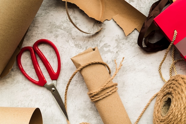 Caixa de presente marrom embrulhado com barbante e tesoura em fundo branco texturizado