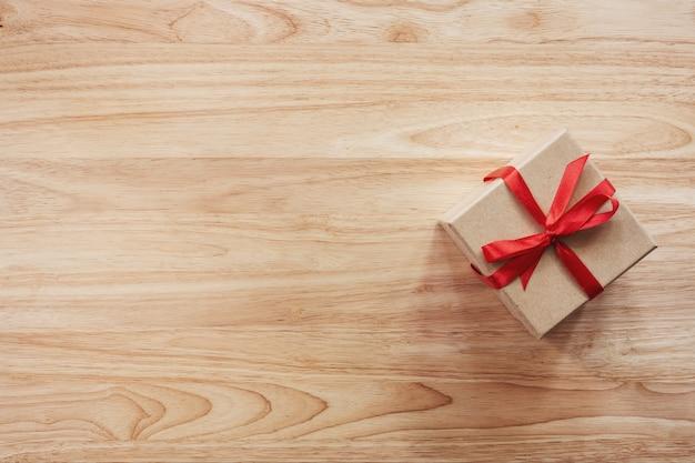 Caixa de presente marrom no fundo da mesa de madeira com espaço de cópia