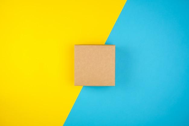 Caixa de presente marrom quadrado sobre um fundo amarelo-azul
